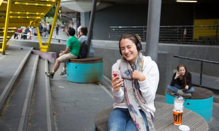 A young woman smiles while she enjoys a call with a friend on her smartphone.