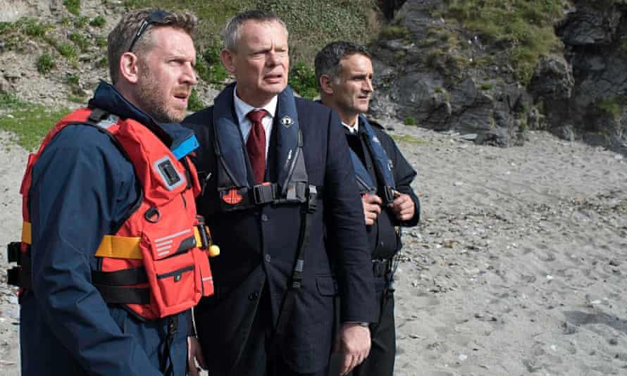 Martin Clunes as Doc Martin with Cornishmen Gerry (Paul Thornley) and PC Joe (John Marquez). Photogr