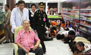 King Bhumibol Adulyadej sitting on a wheelchair as he passes well-wishers at a supermarket located in Siriraj hospital in Bangkok, Thailand.