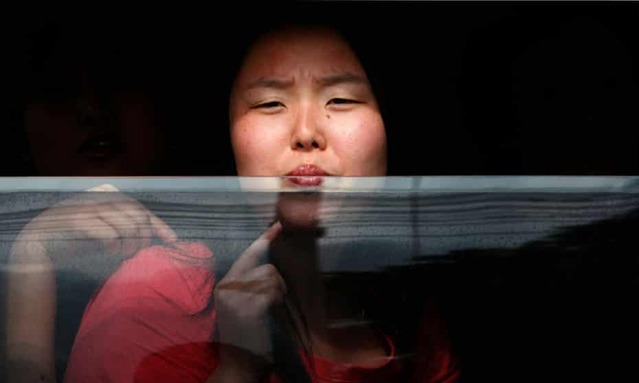 A North Korean defector looks out of a police vehicle while being transported to a Thai court.