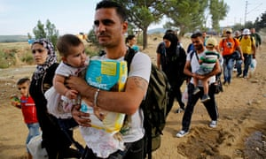 Syrian refugees walk towards a crossing point at Greece's border with Macedonia