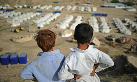 Two boys look out over a large relief camp run by The National Rural Support Program, and aided by Oxfam, UNHCR, Medecins Sans Frontieres, and Diakone at Charsadda on September 23, 2010.