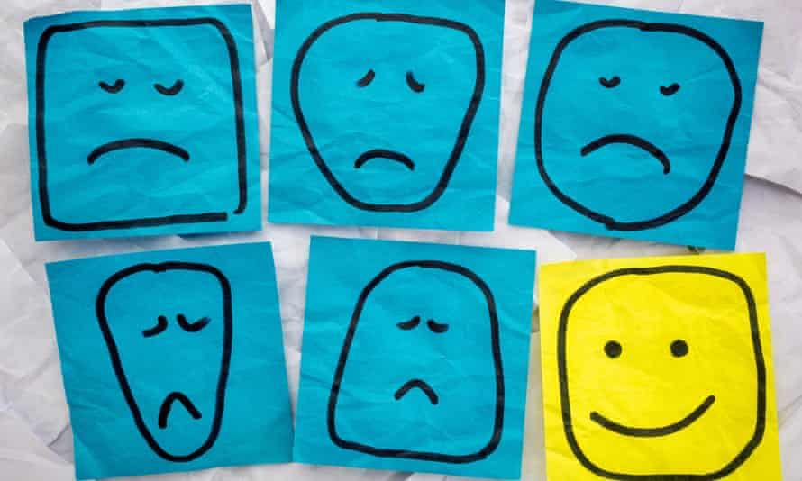 Sad faces on blue sticky notes, happy face on yellow one