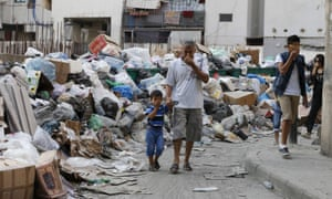 Making a stink: Beirut residents cover their noses as they walk past piled-up rubbish.