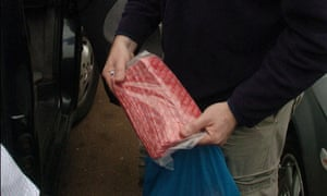 A police officer finds a bag of condoms during a raid