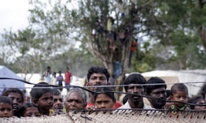 Sri Lankan Tamils look over a fence in a camp