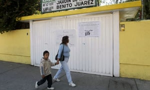 A woman and her son walk past a closed school in Mexico City