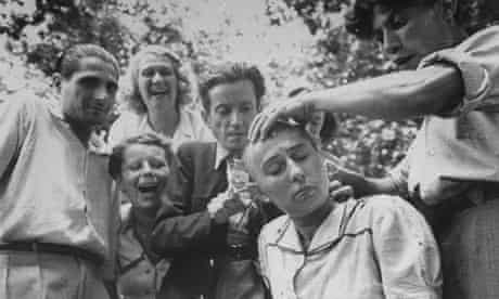 A crowd jeers as a woman's head is shaved during the liberation of Marseilles