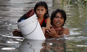Man and his daughter struggle though floodwater in Philippines