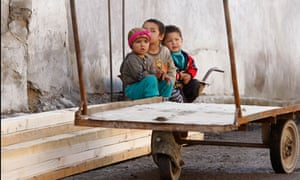 Ethnic Uzbek children sit at their destroyed house in Osh