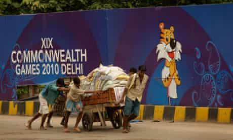 Labourers push cart beside Commonwealth games mascot