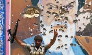 Iraqi soldier poses in front of a mural