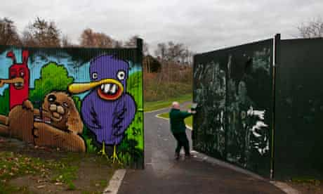 A park employee closing the peace wall in Belfast