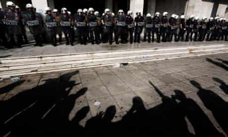 Greek protesters face police following a demonstration in Athens