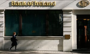 A woman passes a branch of the Bank of Ireland in London