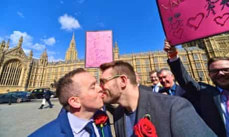 Two men kissing outside the Houses of Parliament