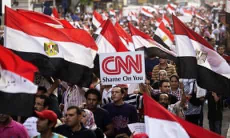 An Egyptian protester with a CNN placard