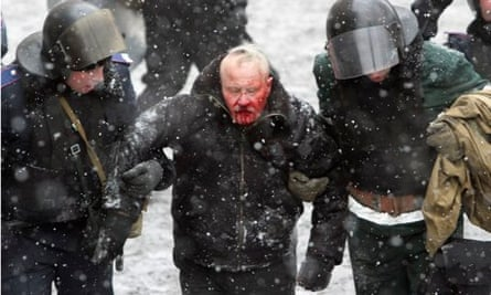 Ukrainian riot police detain a man in Kiev