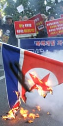South Korean protesters burn North Korea's flag at a demonstration in Seoul against Pyongyang's reported nuclear test