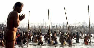 A Hindu pilgrim prays at a ritual bathing site at Sangam at the height of Kumbh Mela