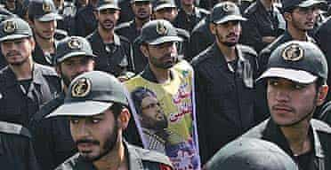 Members of Iran's Revolutionary Guard, one of them covering his chest with a portrait of Lebanon's Hizbullah leader Hassan Nasrallah, take part in a demonstration held in Tehran last year.