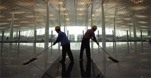 Two workers mop the floor in Beijing airport's newly-built Terminal Three