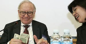 Warren Buffett counts the money from his wallet after an employee asked how much money he had in it, during a meeting with workers of TaeguTec, in Daegu, South Korea.