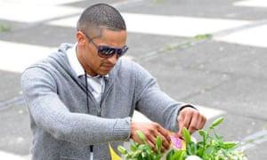 A man leaves flowers outside Marlborough Grange, Leeds, where Pat Regan was killed yesterday