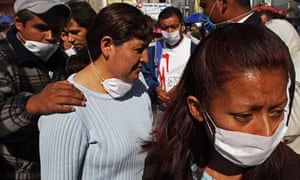 People wear surgical masks as they wait in a line at Mexico City's general hospital