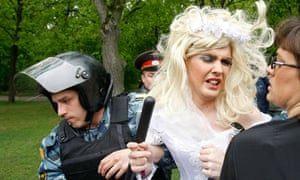 A Russian policeman detains a man dressed in a bridal gown during a gay rights protest in Moscow