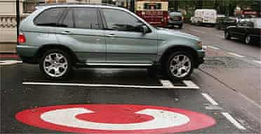 A 4x4 vehicle drives past a congestion charge sign