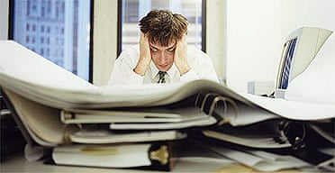 Stressed office worker with piles of paper work on his desk
