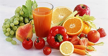 Glass of juice amongst various fruit and vegetables