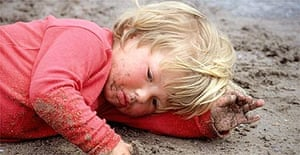 A child getting dirty on the beach