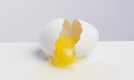 A broken egg with yolk spilling out