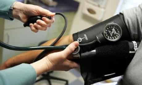 A doctor reads a patient's blood pressure gauge