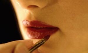 A woman applies lipstick using a lip brush
