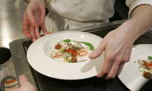 A chef places a dish of food on a tray