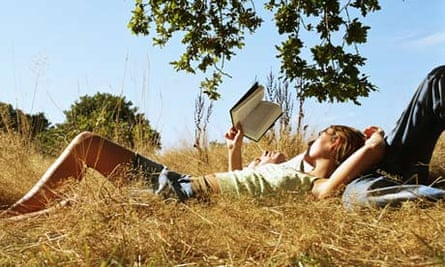 Young couple reading a book under a tree