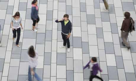 Boy on mobile phone in public square