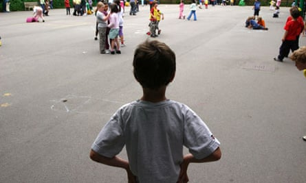 A boy standing alone in the playground
