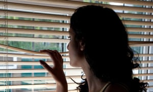 Young woman looking out of a window blind