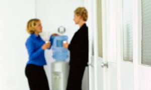 Two women chat around a watercooler