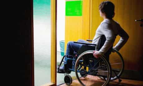 A man in a wheelchair goes through a doorway