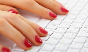 A woman typing on a computer keyboard