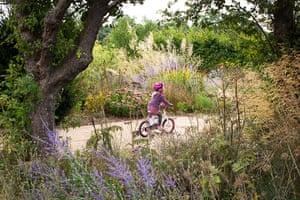 Prairie garden: Kirsty's daughter riding her bike in the garden