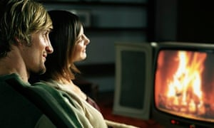 A couple watching a log fire on television