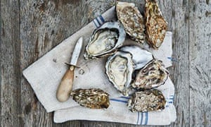 KItchen tips: hold flat-side-up in a cloth, insert oyster knife next to the hinge, work into shell