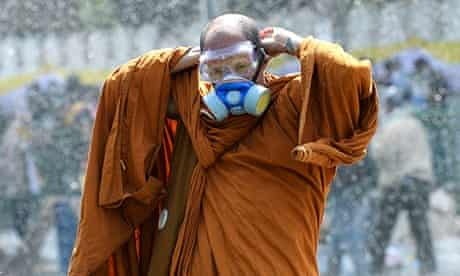A Thai Buddhist monk puts on a gas mask during clashes in Bangkok