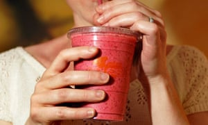 A woman drinking a smoothie